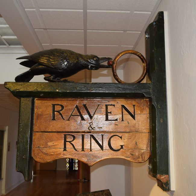 old wooden sign with raven and ring on top of logo