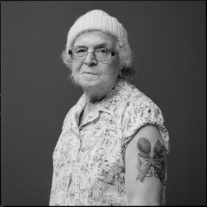 old woman with winter hat and glasses with tattoo of wooden spoons and a bow on her arm